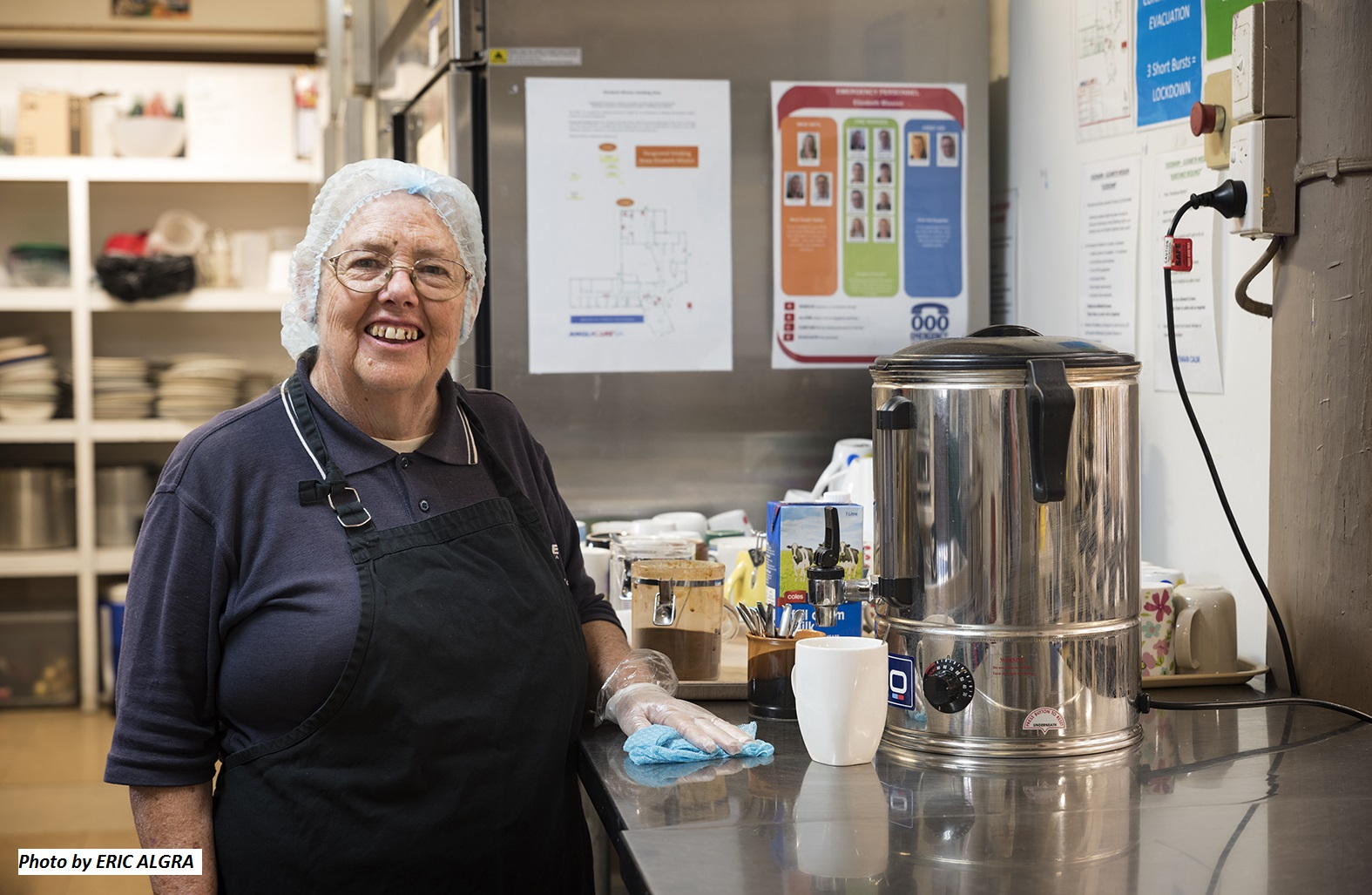 Lady smiling in a kitchen cleaning and making a hot drink