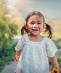 a young girl smiling directly at the camera holding a flower - foster care that changes lives